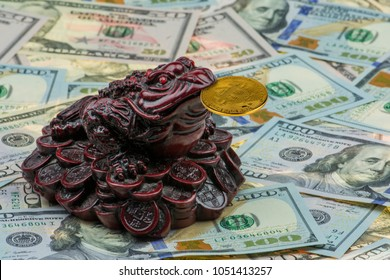 three-legged money toad Jin Chan as a chinese symbol of wealth with gold bitcoin in mouth on variety of US hundred-dollar and fifty-dollar bills. New virtual money. Crypto currency