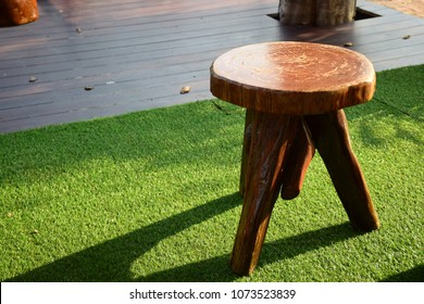 Three-legged wooden chair on artificial grass with sunny