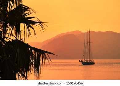A three-masted sailing vessel in a calm bay in the evening