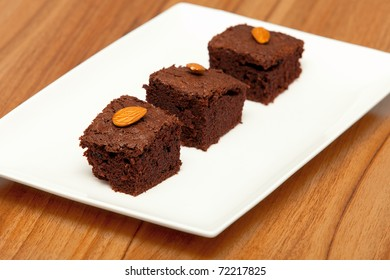Threen brownies with almonds on a white plate
