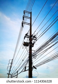 Three-phase electric poles on road side, that is common in Thailand. The electric lines, telephone lines and internet lines are within the same pole. Selective focus and copy space.