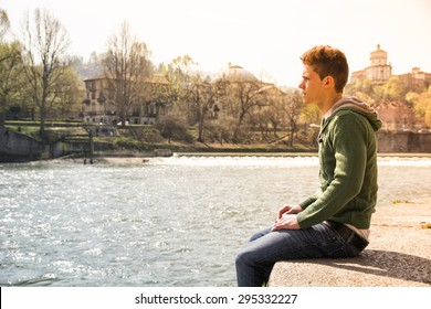 Three-quarter length of contemplative light brown haired teenage boy wearing green hooded-shirt and denim jeans sitting on wall beside picturesque river in Turin, Italy