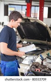 Three-quarter length of mechanic holding a work order