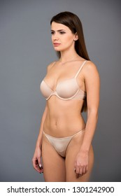 Three-quarter portrait of beautiful brunette women with a slim figure in beige bra and thong. Model snaps in the studio on gray background