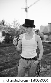 Three-quarter portrait of young man, wearing white top and black classic hat, holding sunglasses, thinking. Black and white picture of creative man on abandoned construction site area. Art-house.