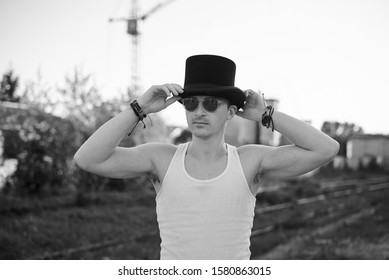 Three-quarter portrait of young man, wearing white top with sunglasses, holding his black classic hat, thinking. Black and white picture of creative man on abandoned construction site area. Art-house.