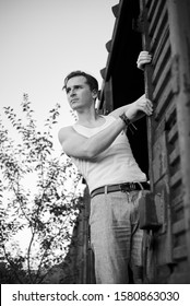 Three-quarter portrait of young man, wearing grey pants, white top, standing inside old railway carriage, holding to doors. Black and white picture of creative man on abandoned train area. Art-house.