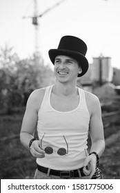 Three-quarter portrait of young man, wearing white top and black classic hat, holding sunglasses, smiling, laughing. Black and white picture of creative man on abandoned construction site area. Art