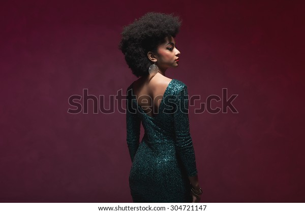 Three-quarter rear view shot of a young woman with Afro hairstyle, wearing elegant sparkling green dress, looking into the distance against maroon background.