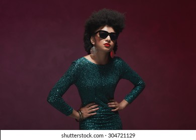 Three-Quarter Shot of a Stylish Young Woman with Afro Hairstyle, wearing Elegant Green Dress with Sunglasses, Posing Against Purple Background.