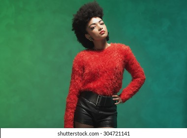 Three-Quarter Shot of a Stylish Young Woman with Afro Hair, Wearing Furry Red Shirt and Black Shorts, Looking at the Camera Against Green Wall