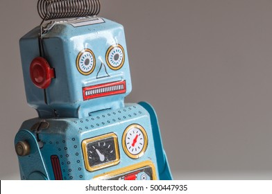 Three-quarter view of a blue and red tin robot toy's head and upper torso, facing to the right, on a blurred gradient background.