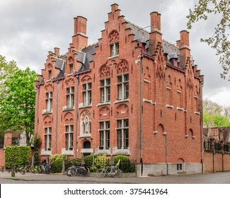 Three-story brick building of the existing Church school, which parked a few bicycles. Near the Beguinage (Begijnhof), Bruges, Belgium.