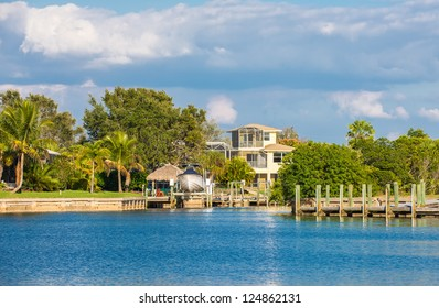 A three-story luxury house with a boat lift on a canal in Southwest Florida, USA, surrounded by oak trees, palm tress and lush lawns.