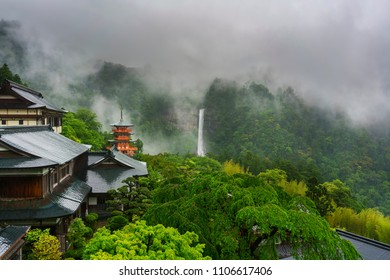 Three-story Sanjudo pagoda of Seiganto-ji temple with Nachi falls and beautiful foggy scenery in the background , listed as a UNESCO World Heritage Site in Wakayama Prefecture , Japan