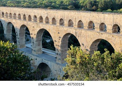 Three-tiered aqueduct Pont du Gard built in Roman times on the river Gardon, Provence, summer sunny evening