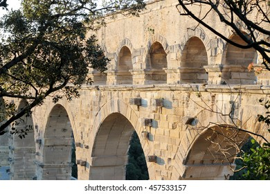Three-tiered aqueduct Pont du Gard built in Roman times on the river Gardon, Provence, summer sunny evening