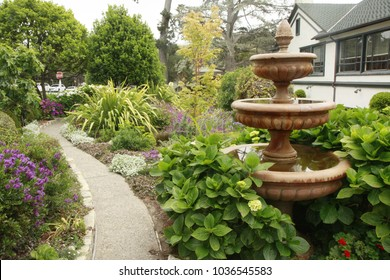 Three-tiered fountain outside in garden next to pathway. Green foliage surrounds fountain, purple flowers on left side of frame. Photo taken in Carmel, California.