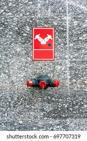 Three-way hose valve for fire protection equipment mounted from building. Exterior granite wall with vivid red splitter hose connector.
