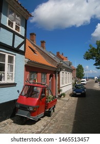 A three-wheeler parked on a cobblestone road in front of old housees in idyllic Danish village