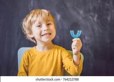 Three-year old boy shows myofunctional trainer. Helps equalize the growing teeth and correct bite, develop mouth breathing habit. Corrects the position of the tongue.