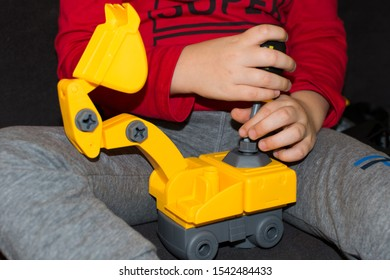 Three-year-old boy'h hand twisting the bolt with a screwdriver.  Practising fine and gross motor skills.
