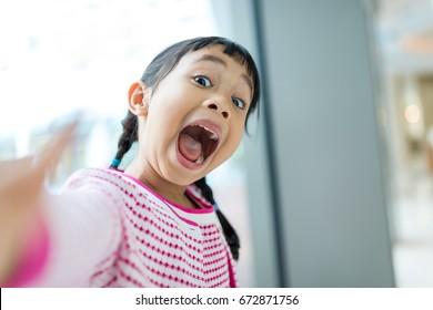 Thrilled asian girl taking selfie