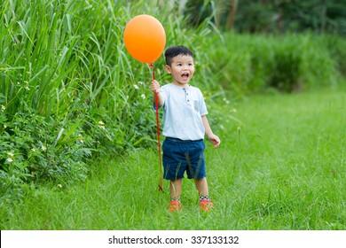 Thrilled little boy holding a flying ballon