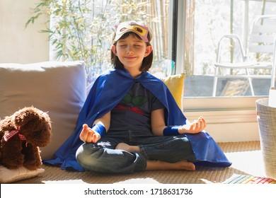 begeisterter Superheld lockerndes Kind mit geschlossenen Augen und Dankbarkeit von Achtsamkeit und Meditation mit Teddybär allein zu Hause, während Corona-Virus-Quarantäne