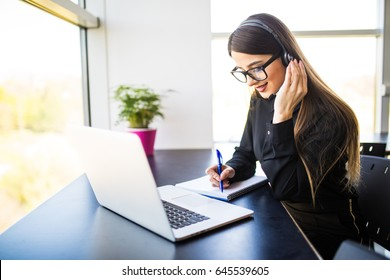 thrilled young female manager taking notes on good news on headset and notebook in office