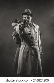 Thriller film noir scene with man pointing a gun and woman hiding behind him