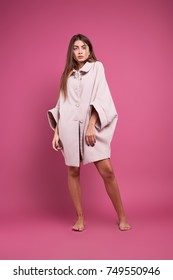 A thrilling girl posing in a beige overcoat over underwear