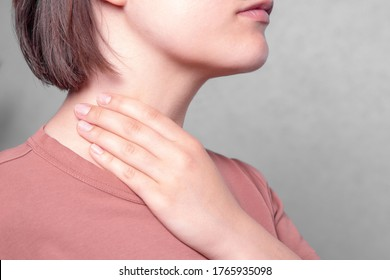 Throat pain. Woman holding her inflamed throat,sick woman with sore throat; portrait of woman suffering from cold, flu, sickness with sore throat inflammation, Medical concept.