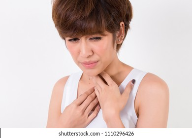 Throat Pain. Woman with sore throat feeling bad. Beautiful young asian girl touching neck with hand. .  Isolated on white background. Studio lighting. Concept for healthy and medical