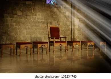 Throne with antique wooden chairs in a dark room with an old stone wall in the background and the rays of sunlight falling from a window, a symbol of power and ruling