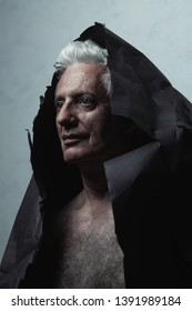 Through the centuries, ancient art concept. Close up portrait of fashionable mature man wearing black paper cloak over light blue background. Silver shiny hair. Graphic shadows. Studio shot