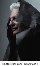 Through the centuries, ancient art concept. Close up profile portrait of fashionable mature man wearing black paper cloak over light blue background. Silver shiny hair. Graphic shadows. Studio shot