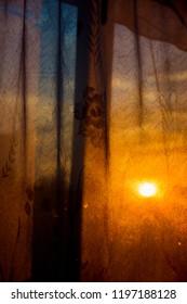 Through the curtain shines the setting sun - Shutterstock ID 1197188128