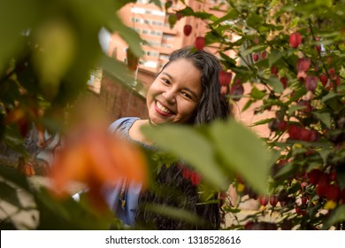 Through a foliage of leaves and flowers you see a smiling and beautiful young woman.
