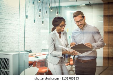 Through glass view of two smiling multi-ethnic business colleagues reviewing paper documents while standing in modern office