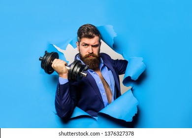 Through paper. Bearded man with dumbbell. Sport. Bearded man through paper. Workout. Fitness. Healthy lifestyle. Discount. Season sales. Copy space for advertising.