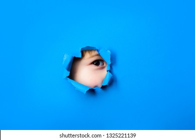 Through paper. Spy.Little boy looking through paper. Spy eye watching through a hole. Child's eye looking through hole. Boy breaks paper. Sale. Discount.
