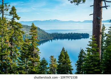 Through pine tree forests Blue morning dream land reflections along Lake Tahoe shoreline a California nature attraction travel destination gorgeous Mountain View's at Emerald Bay cove