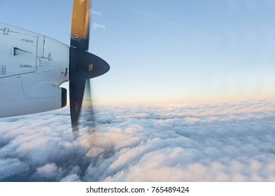 Through plane window propellor spinning blue sky and sunset colors above white cloud