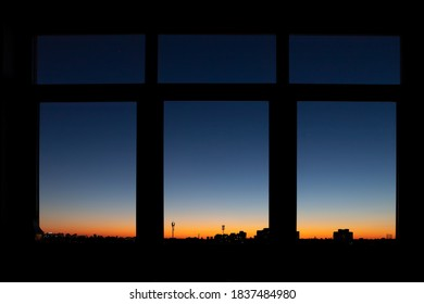 Through triple window POV with scenic city downtown cityscape black building silhouettes against fiery orange to blue dramatic sunset or sunrise on early morning time. Metropolis panoramic background