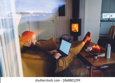 Through window hipster guy working on laptop near burning cozy fireplace with snowy mountains of Norway reflecting on window glass