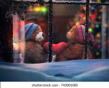 Through the window in the snow looking at plush bears holding a heart. Christmas room with fireplace. The concept of a family holiday, warmth in winter and comfort