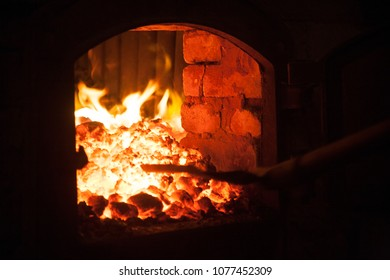 Throw more charcoal on the fire in open iron stove boiler-house
