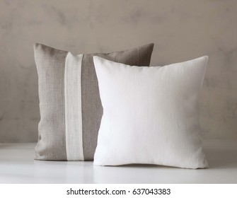 Throw pillows set, white and linen accent pillow in interior.