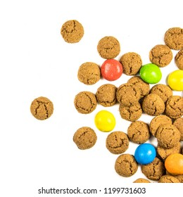 Throw of scattered pepernoten cookies and sweets from above on white background for annual Sinterklaas holiday event in the Netherlands on december 5th